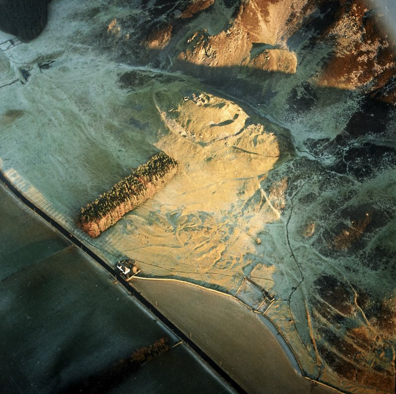 Oblique aerial view centred on the remains of the fort and castle with the remains of the cultivation terraces and enclosure adjacent, taken from the W.