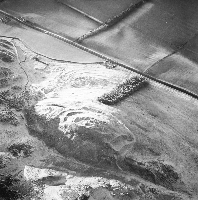 Oblique aerial view centred on the remains of the fort and castle with the remains of the cultivation terraces and enclosure adjacent, taken from the E.