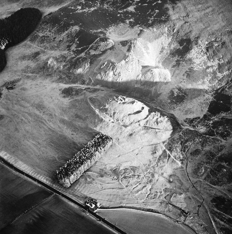 Oblique aerial view centred on the remains of the fort and castle with the remains of the cultivation terraces and enclosure adjacent, taken from the WNW.