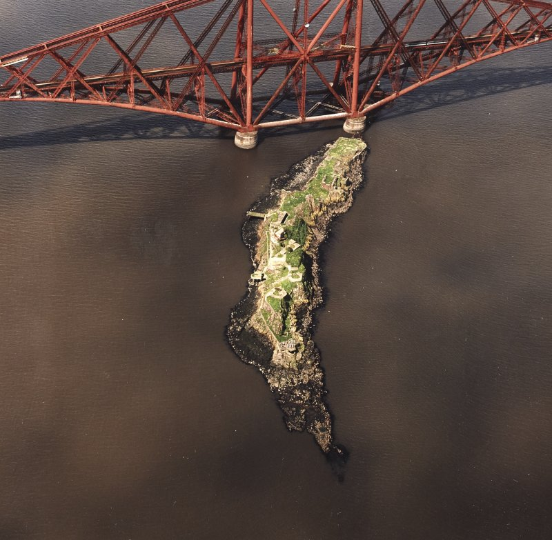 Oblique aerial view of The Forth Bridge and Inch Garvie centred on the rail bridge and the remains of a castle, battery, coast battery and artillery fortifications, taken from the ENE.