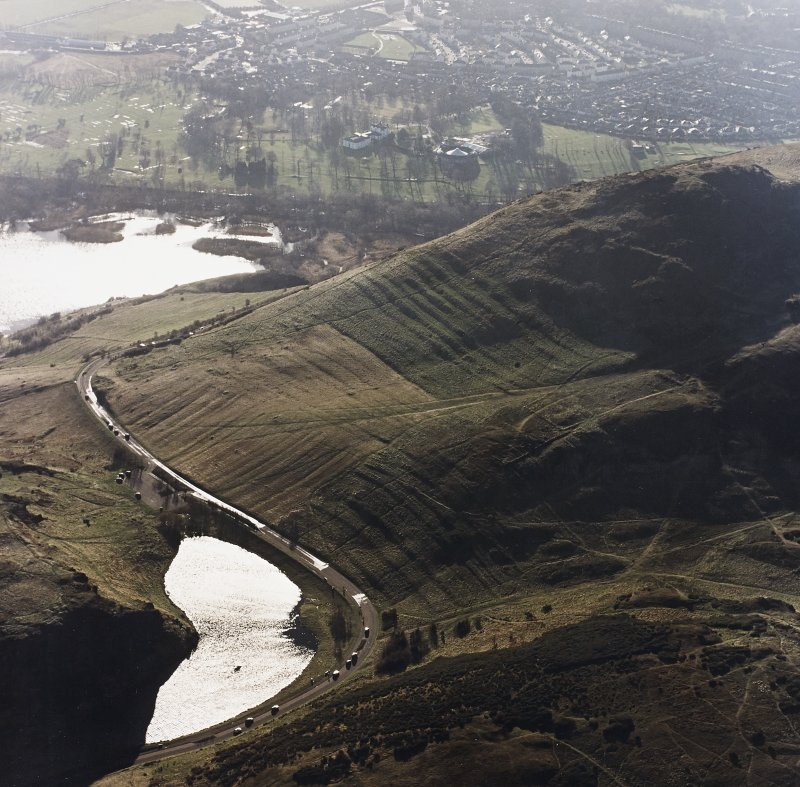 Oblique aerial view of Holyrood Park centred on the remains of cultivation terraces and rig, taken from the NNE.