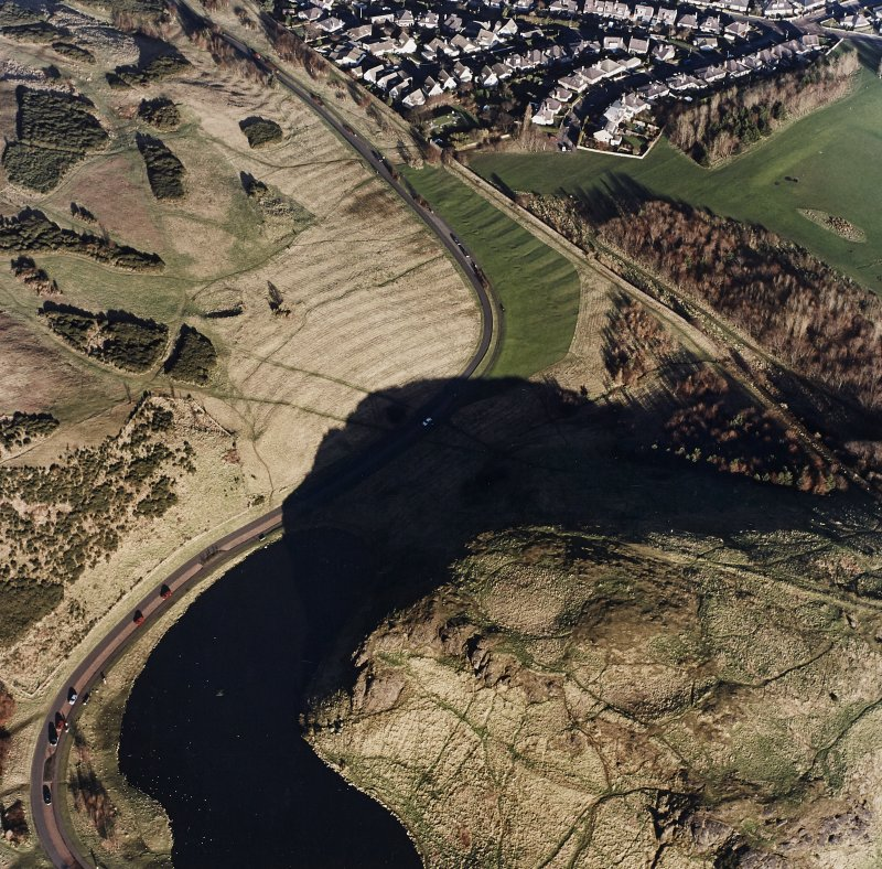Oblique aerial view of Holyrood Park centred on the remains of a fort, field bank and scooped settlement, taken from the SW.