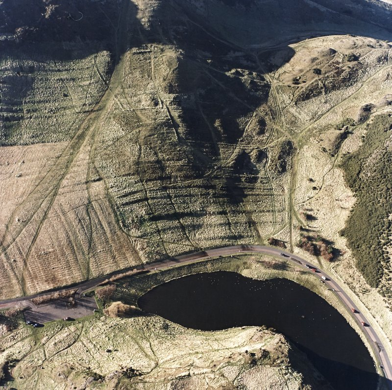 Oblique aerial view of Holyrood Park centred on the remains of cultivation terraces and enclosures, taken from the ENE.
