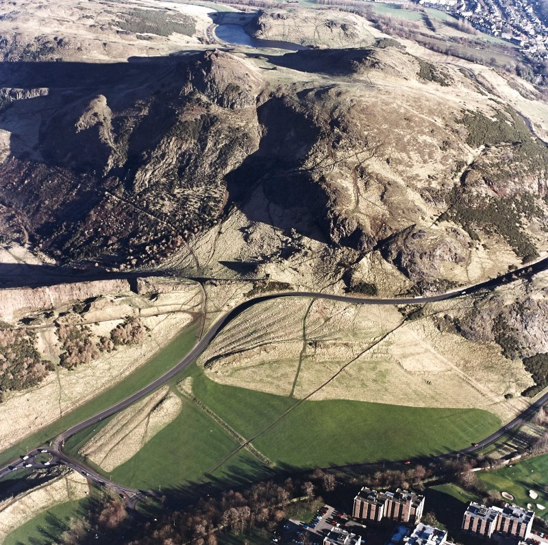 Oblique aerial view of Holyrood Park centred on Arthur's Seat with the remains of cultivation in front, taken from the SW.