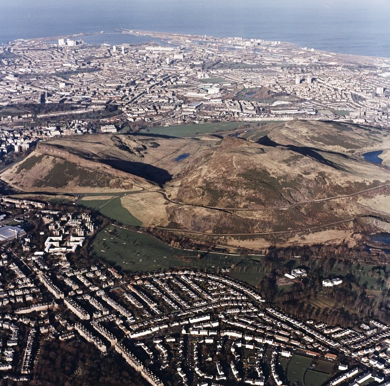 Oblique aerial view of Edinburgh centred on Holyrood Park, taken from the S.