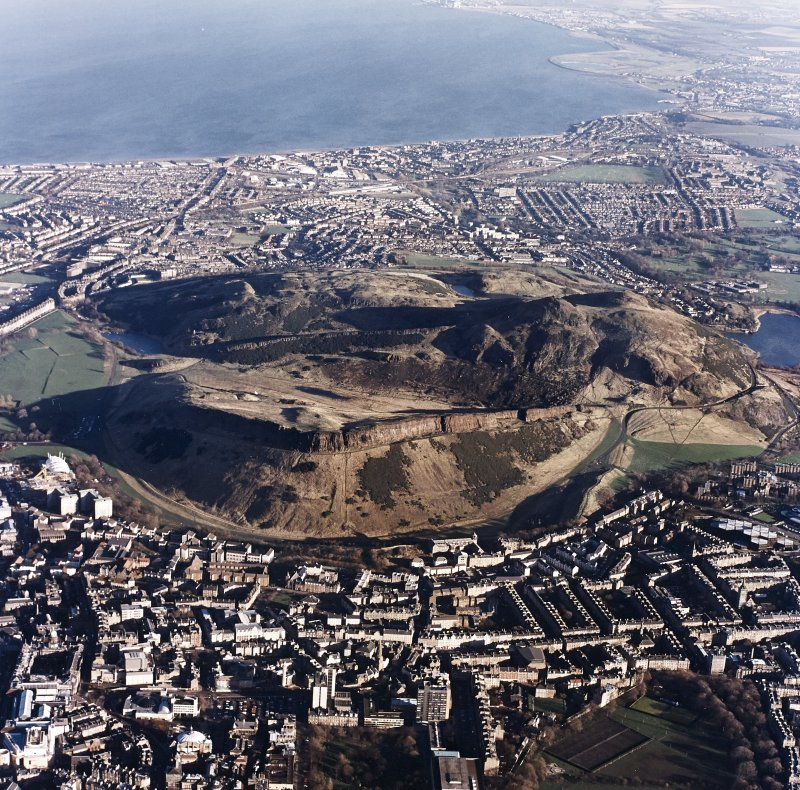 Oblique aerial view of Edinburgh centred on Holyrood Park, taken from the SW.