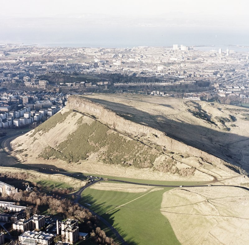 Oblique aerial view of Edinburgh, Holyrood Park centred on the remains of tracks, and Salisbury Crags, taken from the SSE.
