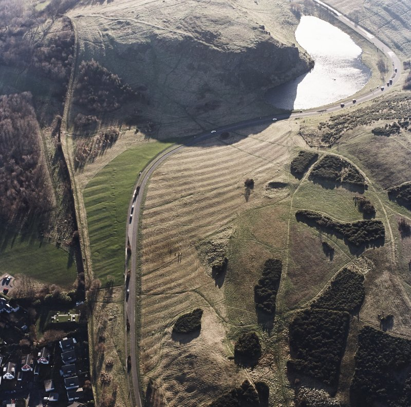 Oblique aerial view of Holyrood Park centred on the remains of rig with a quarry and ring-ditch adjacent, taken from the N.