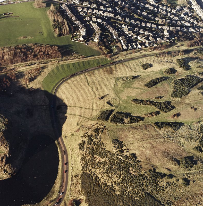 Oblique aerial view of Holyrood Park centred on the remains of rig with a quarry and ring-ditch adjacent, taken from the WSW.