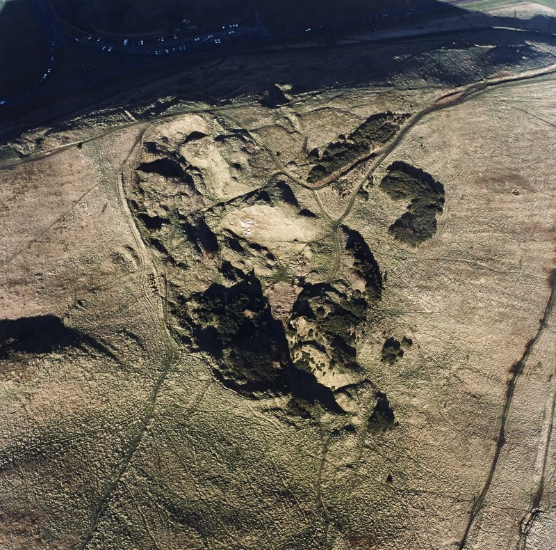 Oblique aerial view of Holyrood Park centred on the remains of quarries, taken from the S.