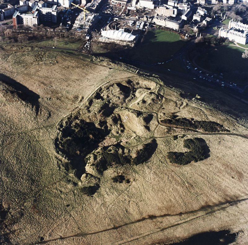 Oblique aerial view of Holyrood Park centred on the remains of quarries, taken from the SE.