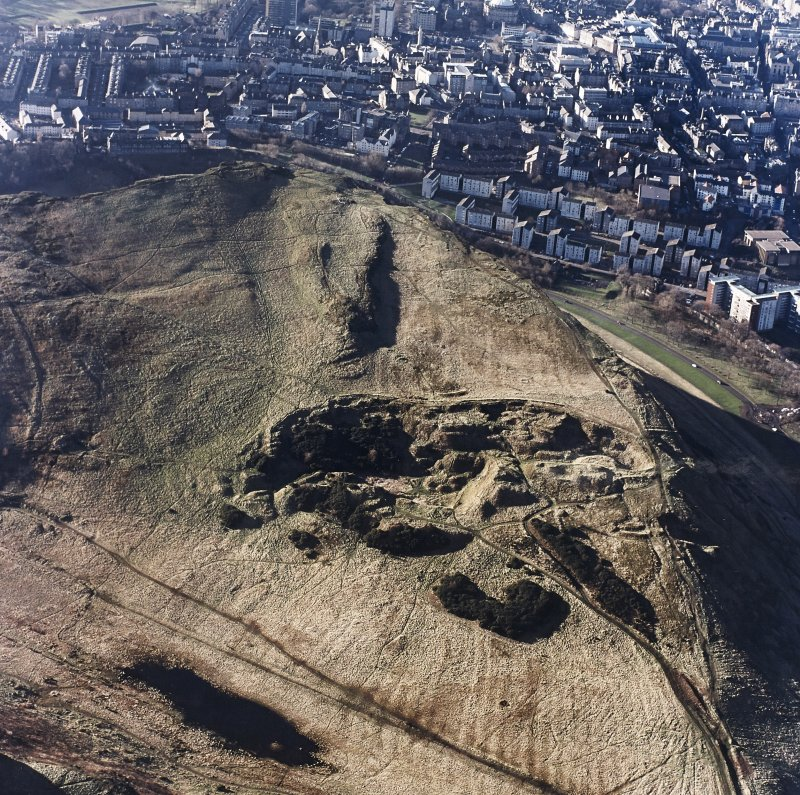 Oblique aerial view of Holyrood Park centred on the remains of quarries, taken from the ENE.