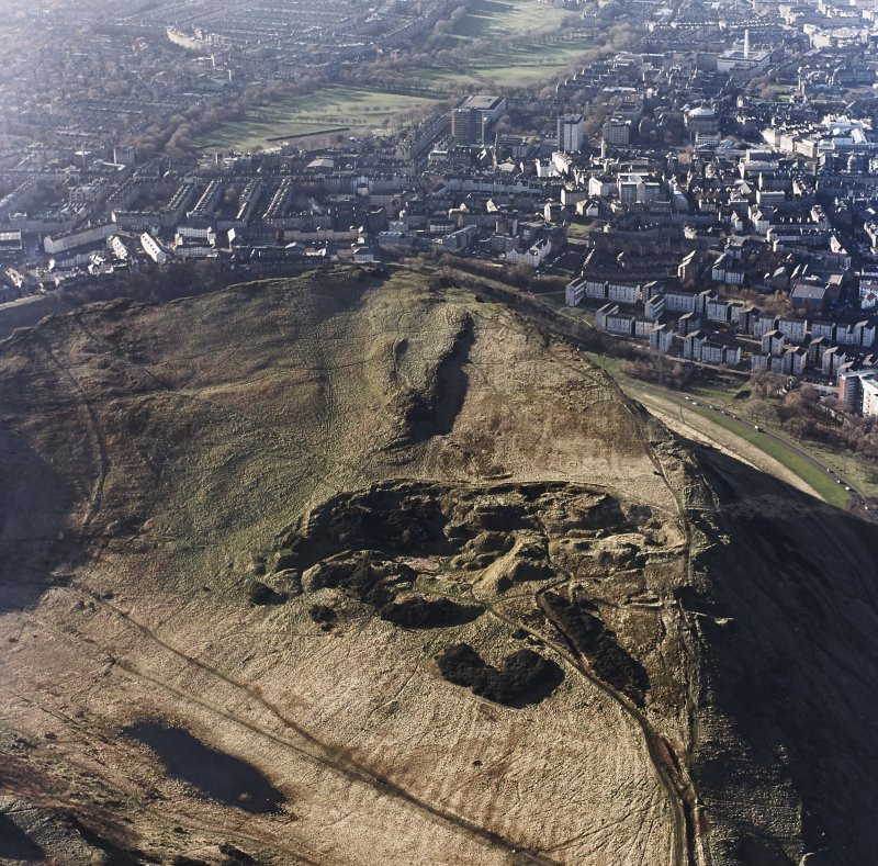 Oblique aerial view of Holyrood Park centred on the remains of quarries with a fort and bank adjacent, taken from the ENE.