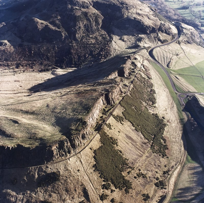 Oblique aerial view of Holyrood Park centred on the remains of quarries on Salisbury Crags, taken from the W.