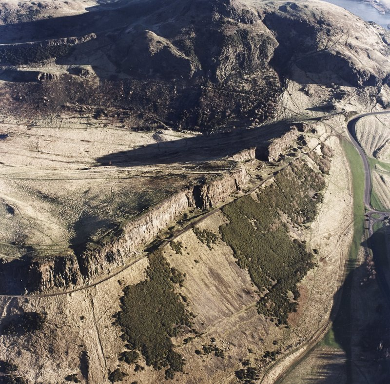 Oblique aerial view of Holyrood Park centred on the remains of quarries on Salisbury Crags, taken from the WSW.