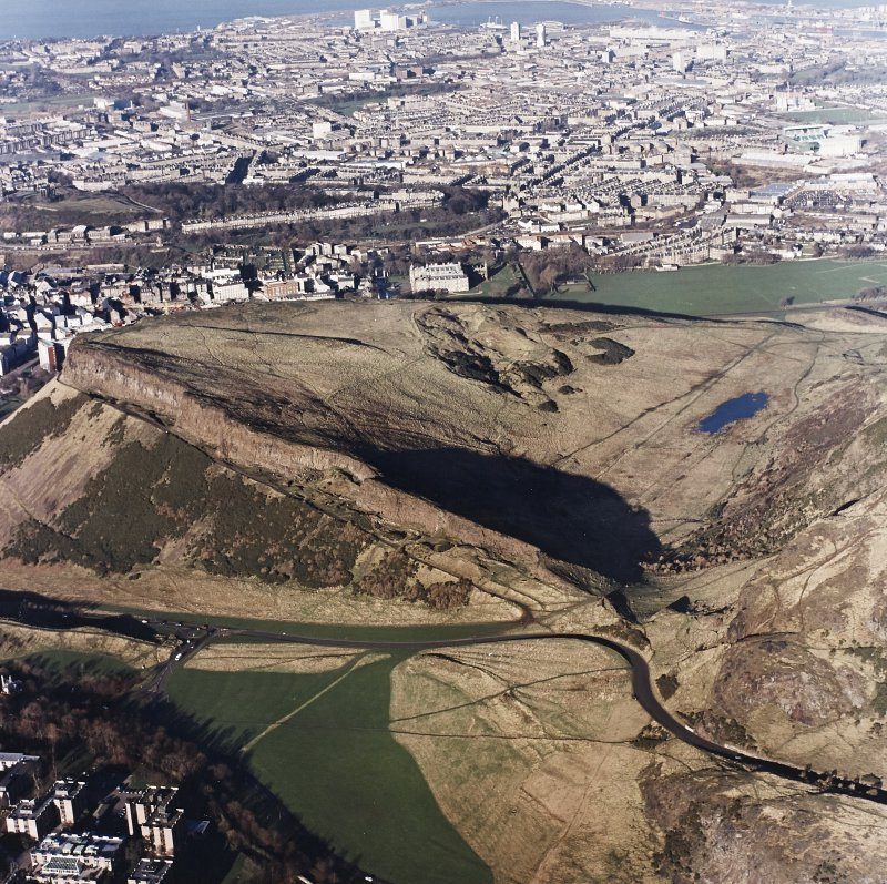 Oblique aerial view of Holyrood Park centred on the remains of quarries on Salisbury Crags with cultivation remains below, taken from the S.