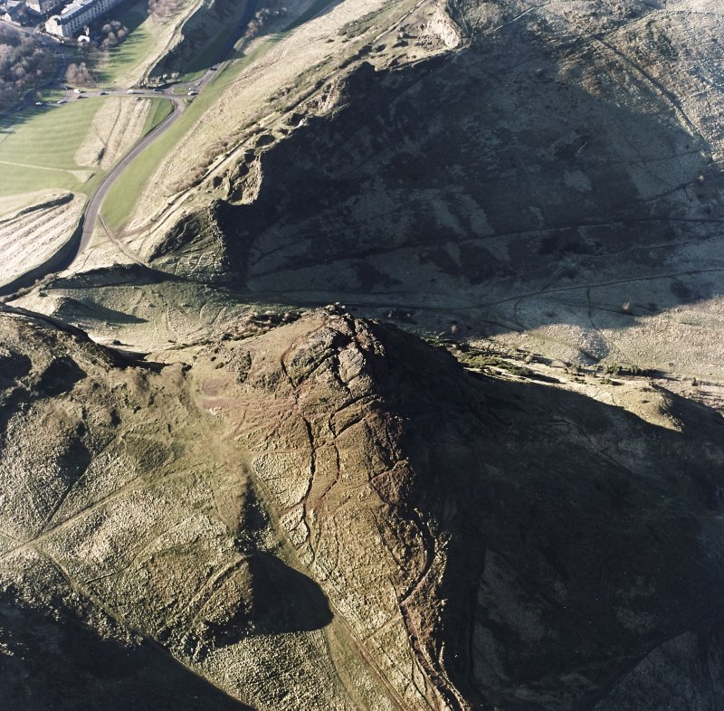 Oblique aerial view of Holyrood Park centred on Arthur's Seat, taken from the ENE.