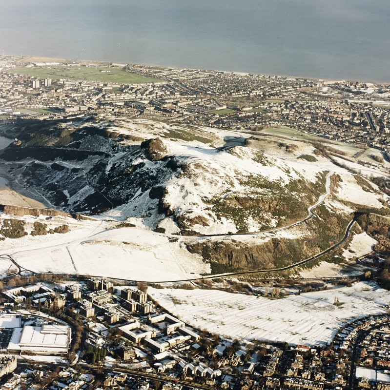 Oblique aerial view of Edinburgh, centred on Holyrood Park, taken from the SSW.