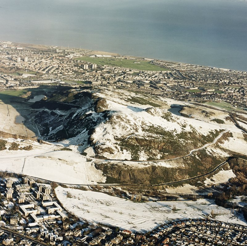 Oblique aerial view of Edinburgh, centred on Holyrood Park, taken from the S.