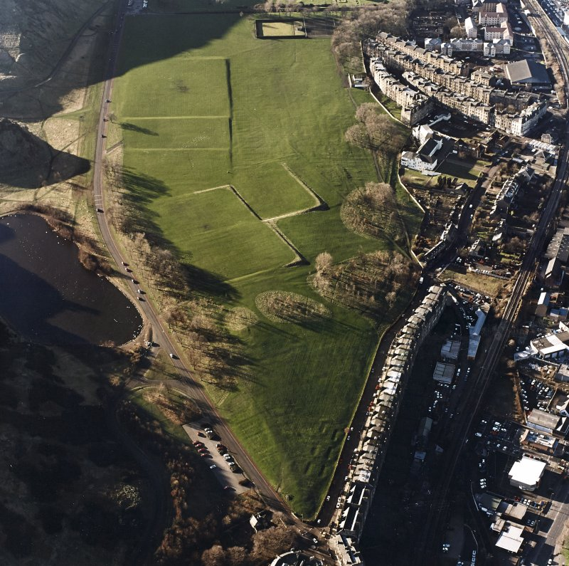 Oblique aerial view of Holyrood Park centred on possible air raid shelters with rig and a parade ground adjacent, taken from the ENE.