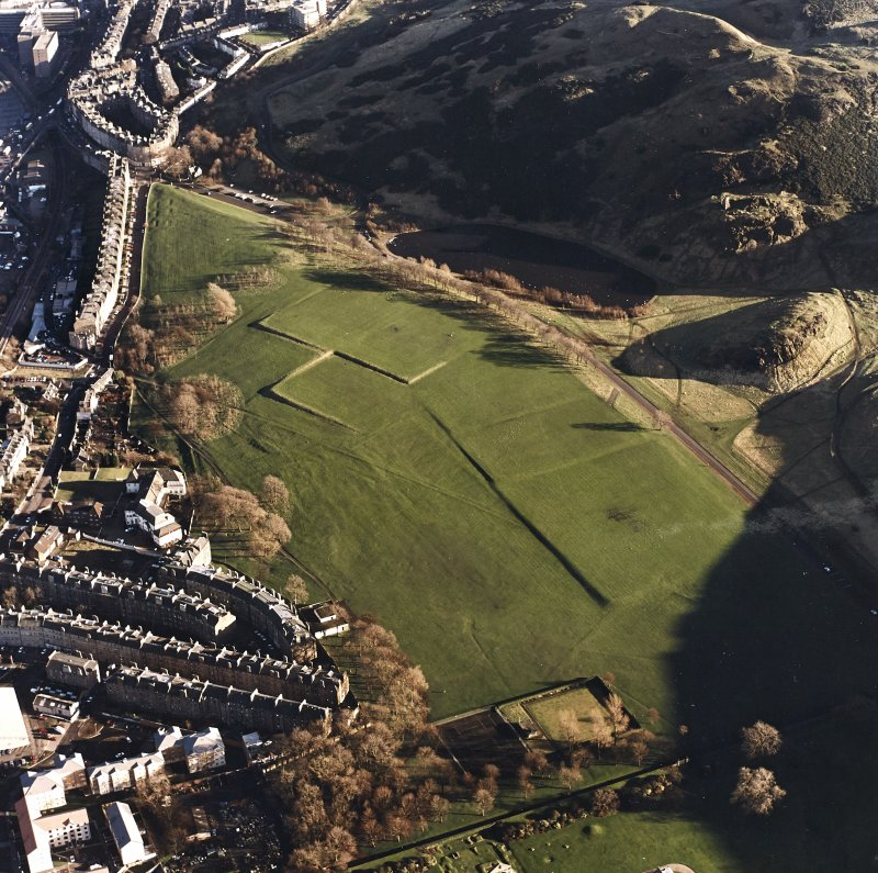 Oblique aerial view of Holyrood Park centred on a parade ground with rig adjacent, taken from the W.