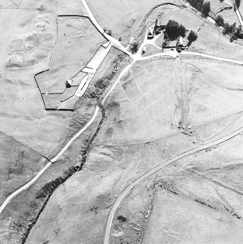 Oblique aerial view centred on the remains of the deserted settlement with the remains of the castle and possible farmstead  adjacent, taken from the NE.