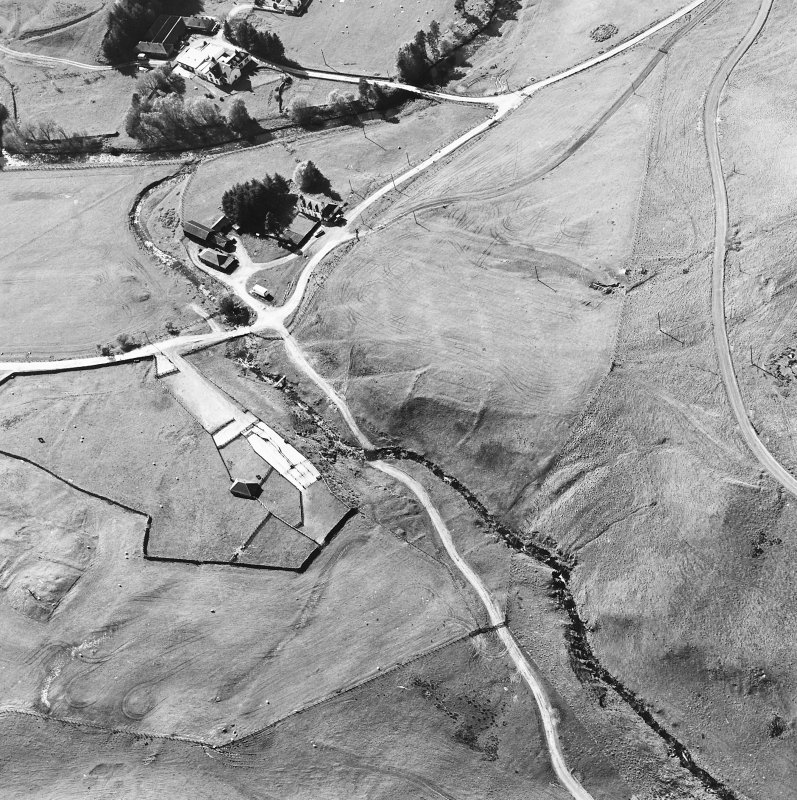 Oblique aerial view centred on the remains of the deserted settlement with the remains of the castle and possible field-system adjacent, taken from the SE.