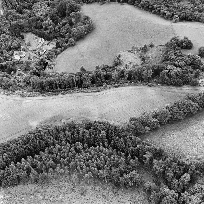 Oblique aerial view of Braidwood centred on linear cropmarks with two churches and a session-house visible in the upper left, taken from the N.