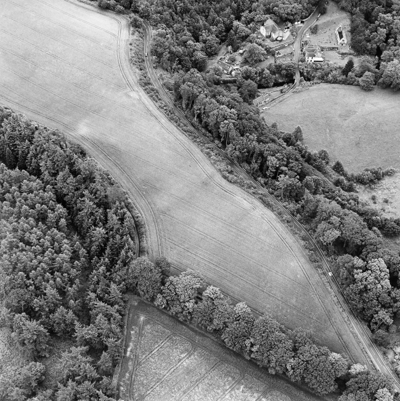 Oblique aerial view of Braidwood centred on linear cropmarks with two churches and a session-house visible in the upper right, taken from the NW.