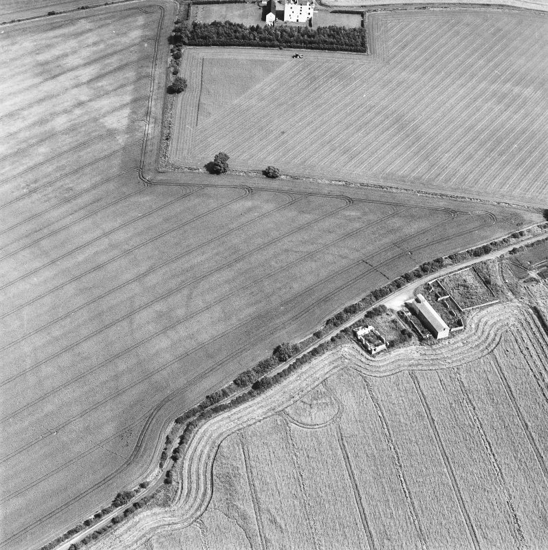 Oblique aerial photograph centred on the cropmark of a fort, taken from the SW. Falside castle is visible in the top centre of the photograph.
