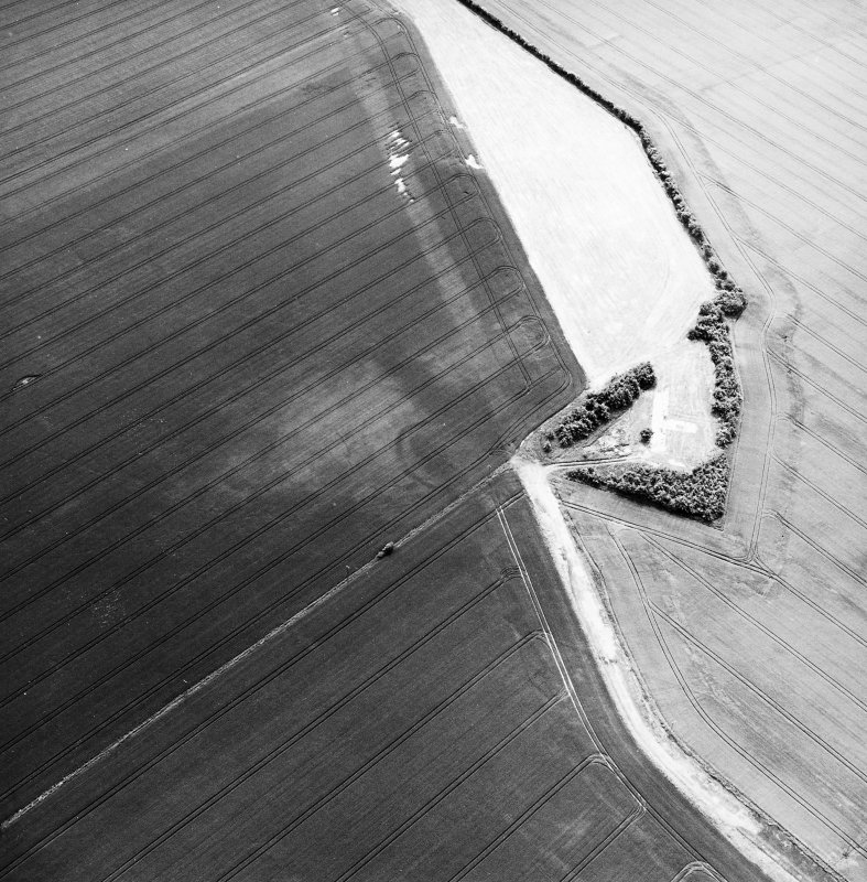 Greendykes, oblique aerial view, taken from the NNE, centred on the cropmarks of a settlement adjacent to the footings of buildings related to MacMerry Airfield.