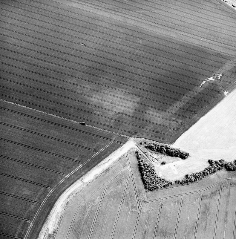 Greendykes, oblique aerial view, taken from the NW, centred on the cropmarks of a settlement adjacent to the footings of buildings related to MacMerry Airfield.