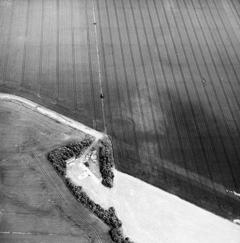 Greendykes, oblique aerial view, taken from the WSW, centred on the cropmarks of a settlement adjacent to the footings of buildings related to MacMerry Airfield.