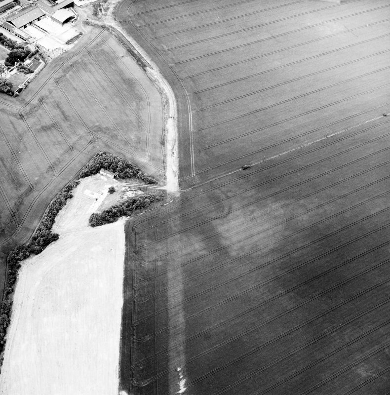 Greendykes, oblique aerial view, taken from the S, centred on the cropmarks of a settlement adjacent to the footings of buildings related to MacMerry Airfield.