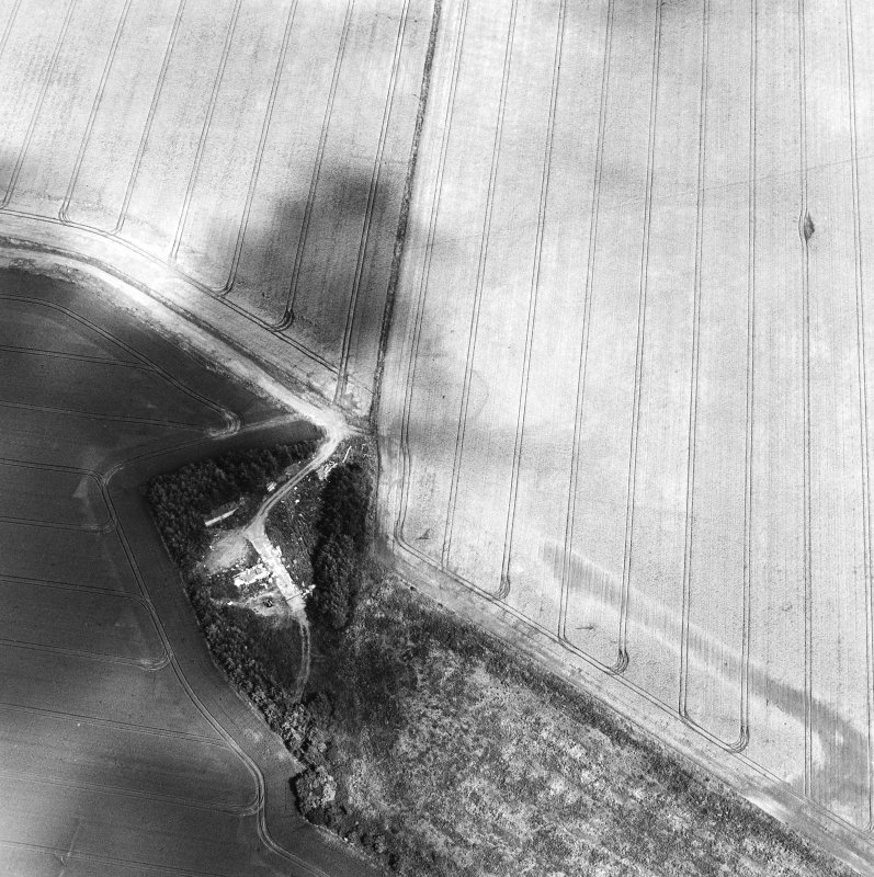 Oblique aerial view centred on the cropmarks of the settlement with the remains of buildings adjacent, taken from the WSW.