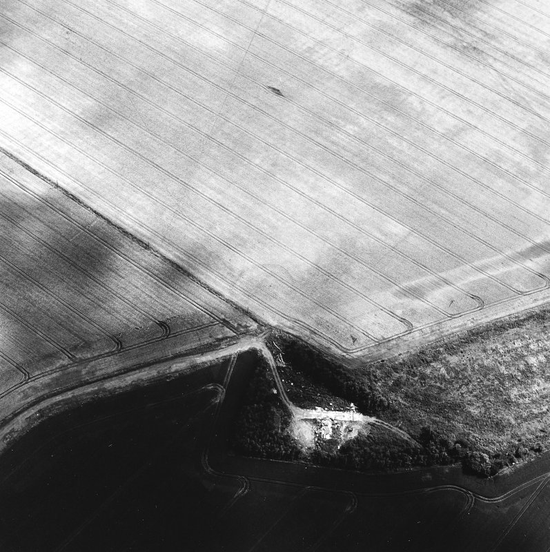 Oblique aerial view centred on the cropmarks of the settlement with the remains of buildings adjacent, taken from the WNW.