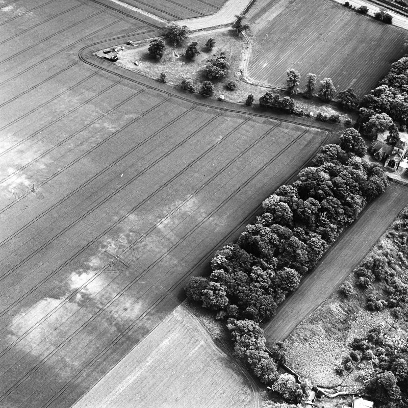 Seton Chapel, oblique aerial view, taken from the NW, centred on the cropmarks of a ring-ditch and pits. Seton Collegiate Church is visible in the centre right of the photograph.