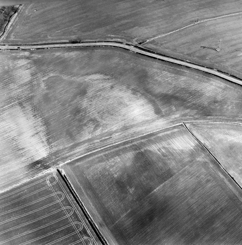 Oblique aerial view of Grizzlefield centred on the soilmarks of a possible enclosure with a standing stone adjacent, taken from the NW.