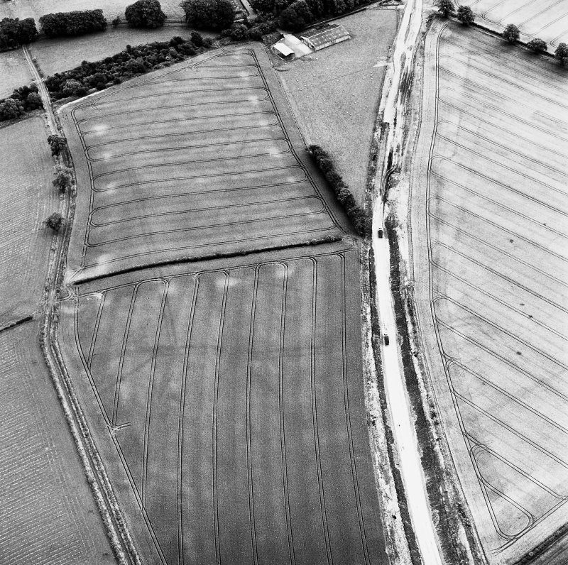 Newstead, oblique aerial view, taken from the W, centred on the southern annexe and a temporary camp. The Newstead by-pass (under construction) runs across the photograph.