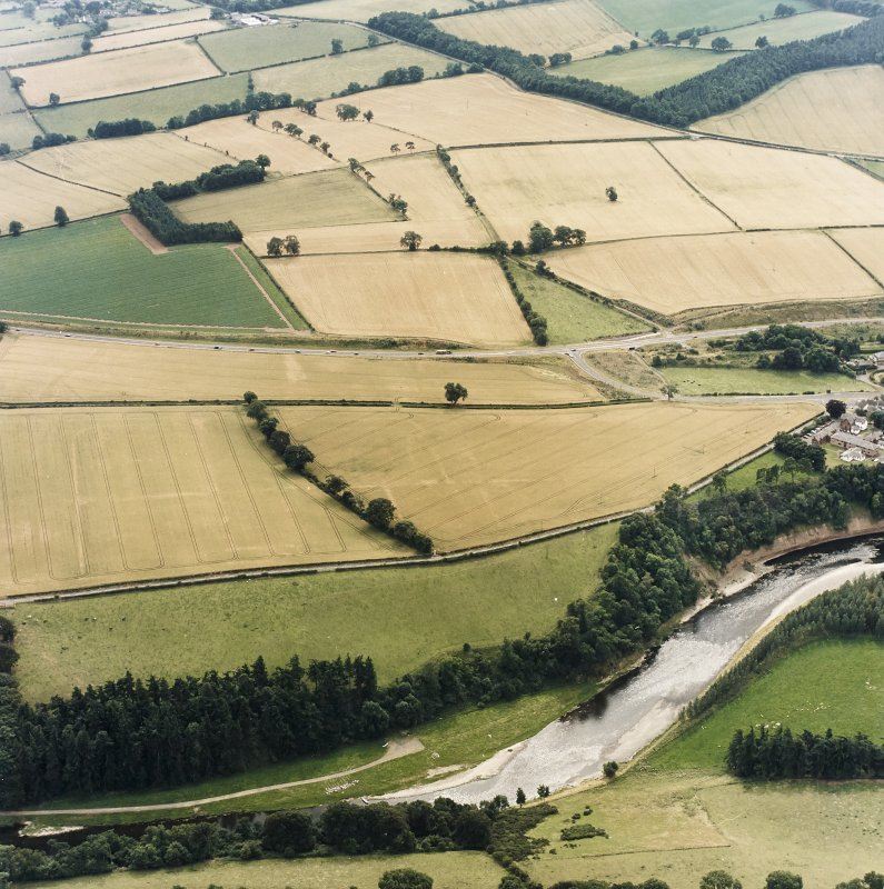 Oblique aerial view of Newstead centred on the cropmarks of the Roman fort, southern and western annexes, taken from the SW.