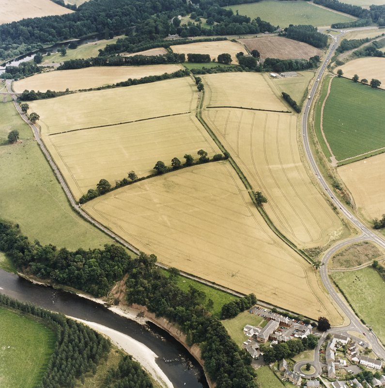 Oblique aerial view of Newstead centred on the cropmarks of the Roman fort, annexes, and Roman temporary camps, taken from the WNW.