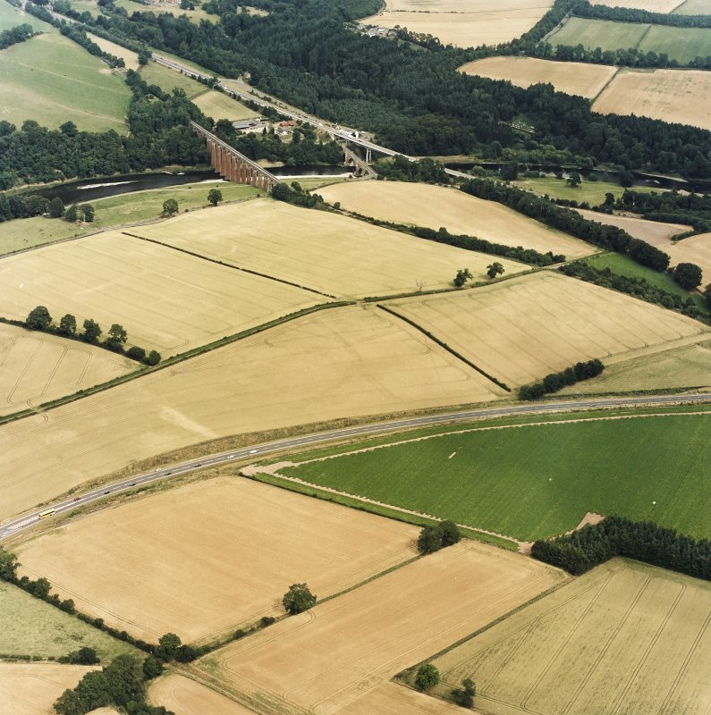 Oblique aerial view of Newstead centred on the cropmarks of the Roman fort, annexes, and Roman temporary camps, taken from the SW.