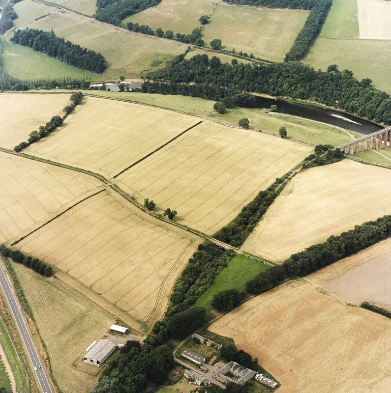 Oblique aerial view of Newstead centred on the cropmarks of the eastern annexe, enclosure and Roman temporary camps with Roman fort adjacent, taken from the SE.