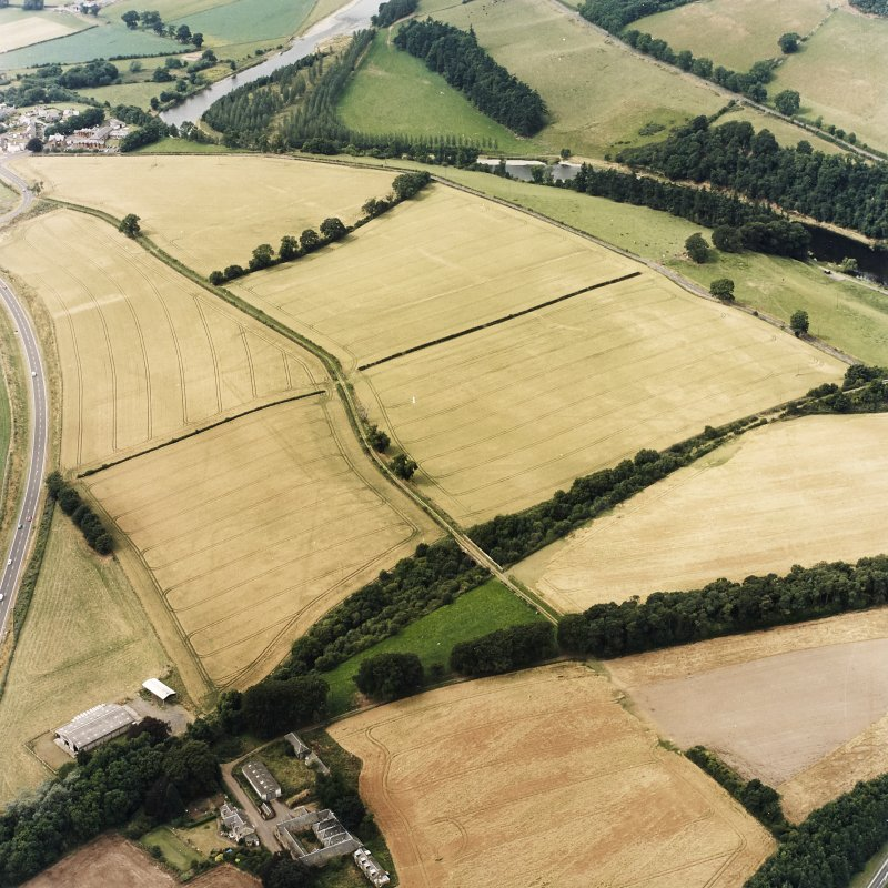 Oblique aerial view of Newstead centred on the cropmarks of the Roman fort, eastern and southern annexes, enclosure and Roman temporary camps, taken from the ESE.
