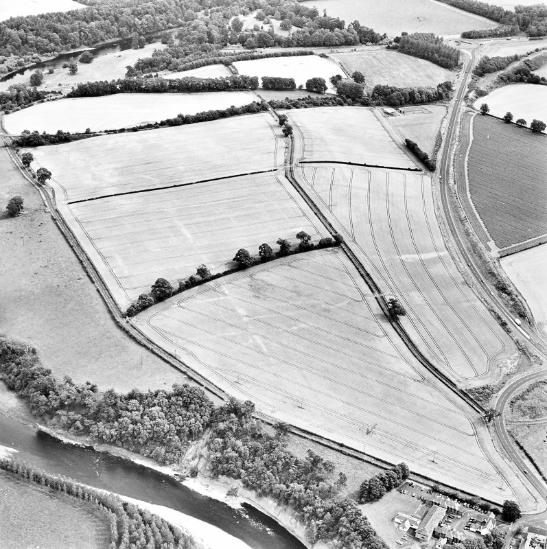 Oblique aerial view of Newstead centred on the cropmarks of the Roman fort, annexes, and Roman temporary camps, taken from the W.