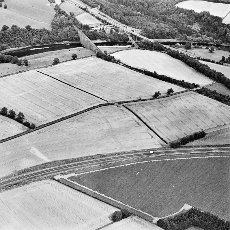 Oblique aerial view of Newstead centred on the cropmarks of the Roman fort, eastern and southern annexes, enclosure and Roman temporary camps, taken from the SW.
