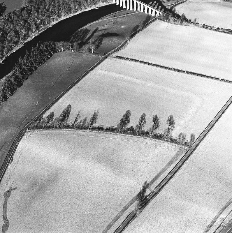 Oblique aerial view centred on the soilmarks of the Roman fort, taken from the SW.