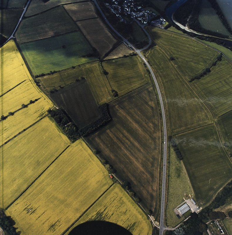 Oblique aerial view centred on the cropmarks of the Roman temporary camps and enclosure with the Roman fort and annexes adjacent, taken from the E.