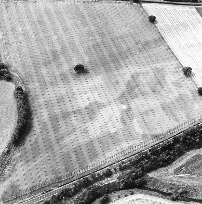 Oblique aerial view centred on the cropmarks of the pit-defined enclosure and field boundary, taken from the ENE.