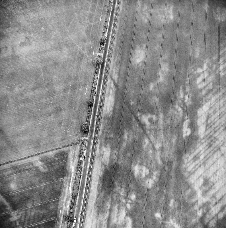 Oblique aerial view centred on the cropmarks of the Roman temporary camp, taken from the NNW.